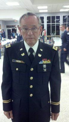 Man in glasses and dress uniform looks into camera, standing in large room