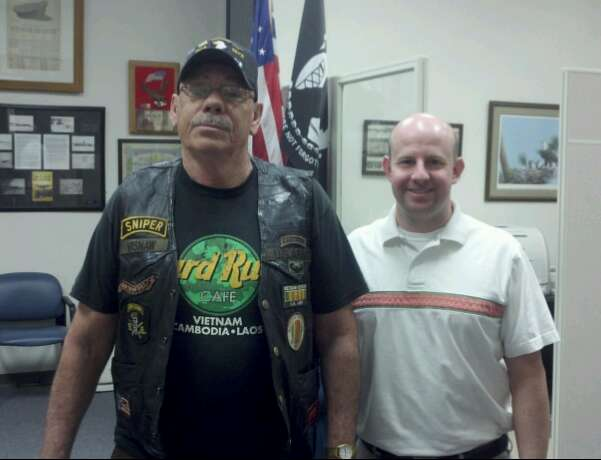 Man in Vietnam Veteran garb and Sniper patch stands beside Nathan Weinbaum in office