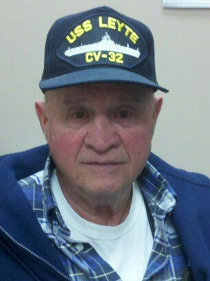 Up close image of older man wearing USS Leyte hat, looking into camera