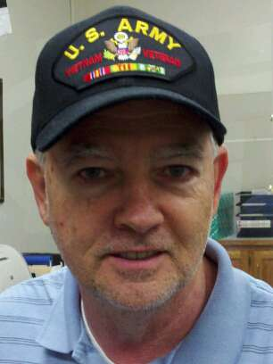 Up close image of man with glasses wearing US Army Vietnam Veteran hat