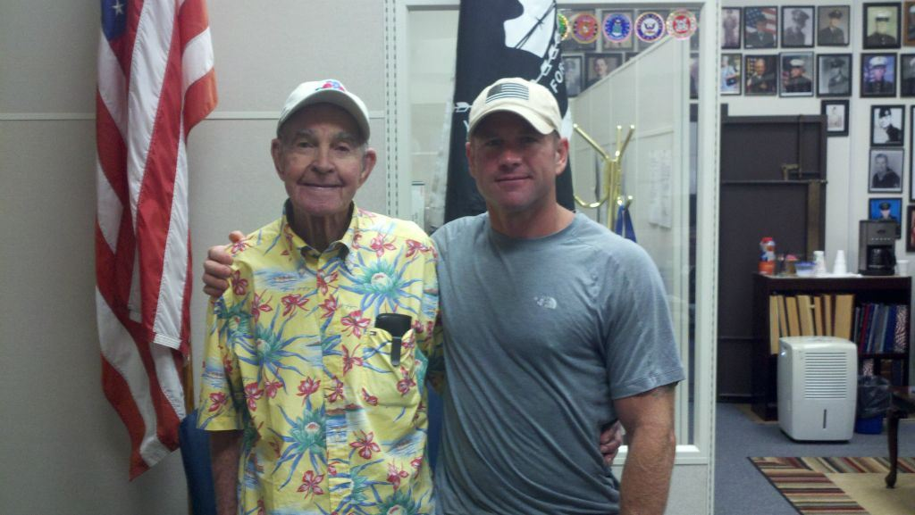 Man in yellow tropical shirt and baseball hat side hugs man in grey shirt and American flag hat, standing in office