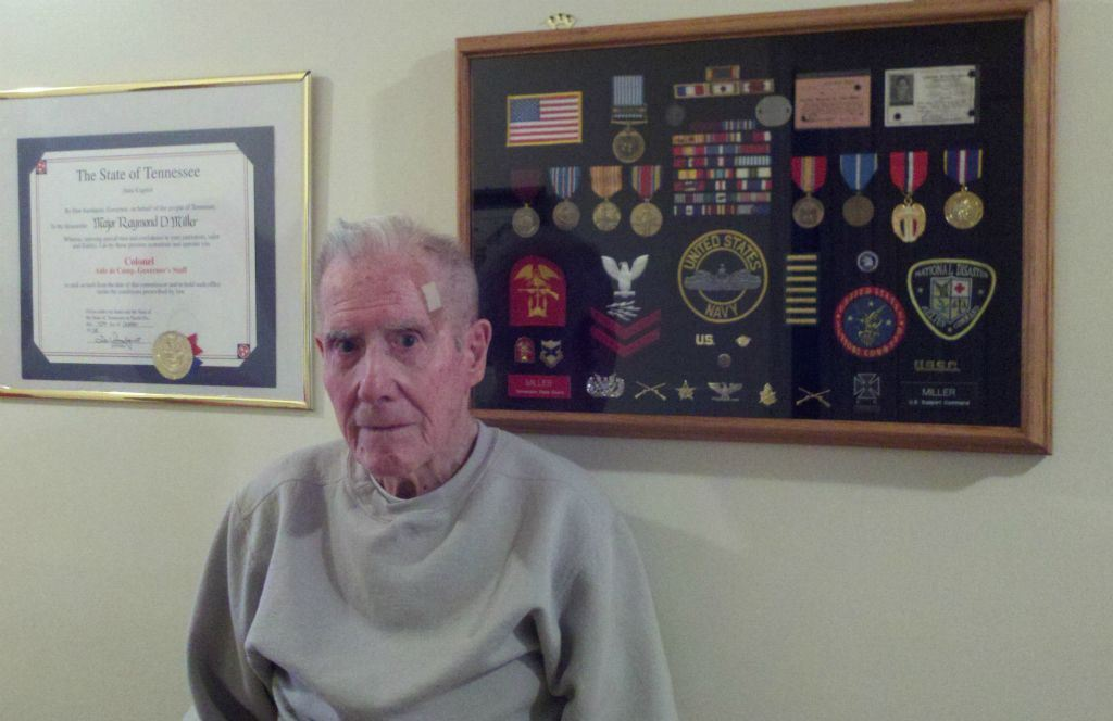 Man in grey sweater stands in front of frame containing medals and pins and patches from Navy