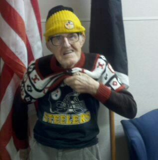 Man in yellow hat and glasses, holds up sweater to reveal a Steelers shirt