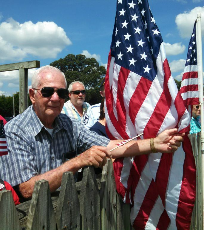 Man in blue plaid and sunglasses leans on wooden fence, holding American flag