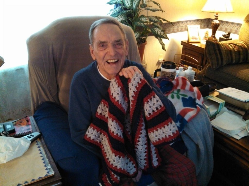 Veteran sitting at home in chair, smiles while holding up red, white, and dark blue knitted blanket