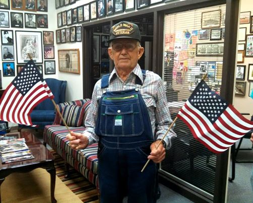 Man stands in office, in overalls and glasses, an American flag in each hand, on his head is a hat with World War II Veteran