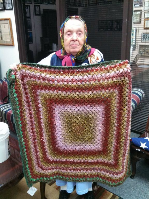 Woman wears scarf around her head, standing, she is holding a erd, pink, brown, and gree quilt