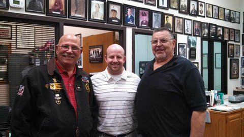 Three men stand together for picture at Veterans Affairs office, looking into camera smiling