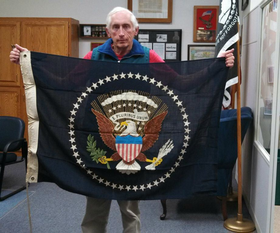 Man in green vest holds up vintage E Pluribus Unum flag with eagle