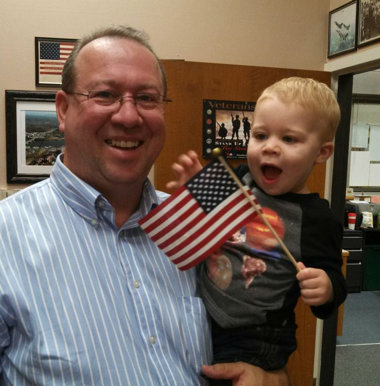 Man in striped shirt and glasses, smiles holding toddler who is happily playing with a miniature American flag