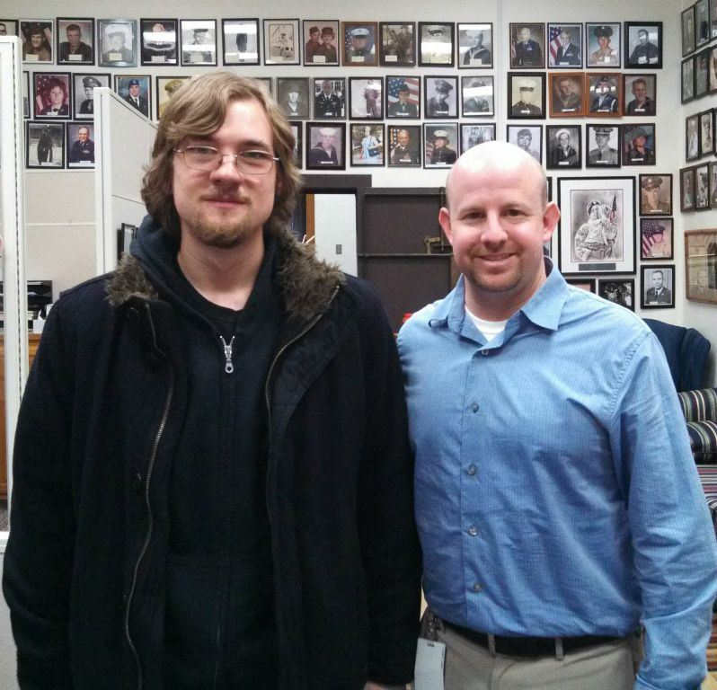 Nathan Weinbaum in blue shirt stands beside young man with long hair and glasses in black coat, looking into camera smiling