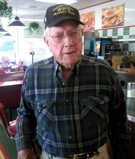 Up close image of man in plaid shirt and glasses, at a restaurant, wearing a WWII 4th Infantry Division hat