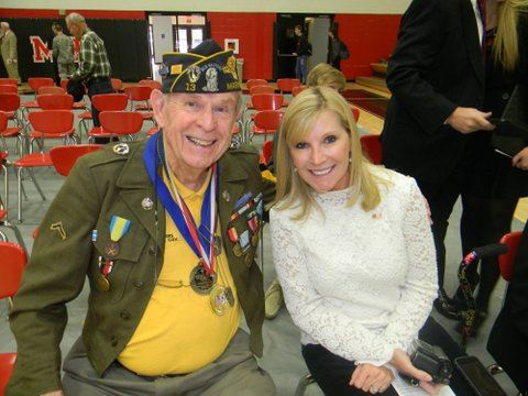 Man wearing yellow shirt, army jacket, cap, and medals smile into camera sitting beside young woman in white shirt