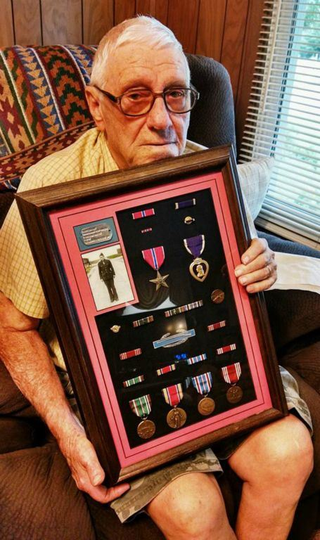Man with glasses sits in chair, holding frame with self portrait, dog tags, and medals