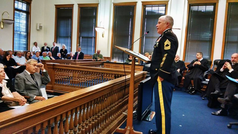 Man in dress uniform stands at podium addressing judges and a court room