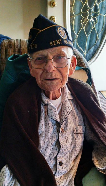 Up close imagae of veteran sitting in chair, with glasses, and Kent Island cap
