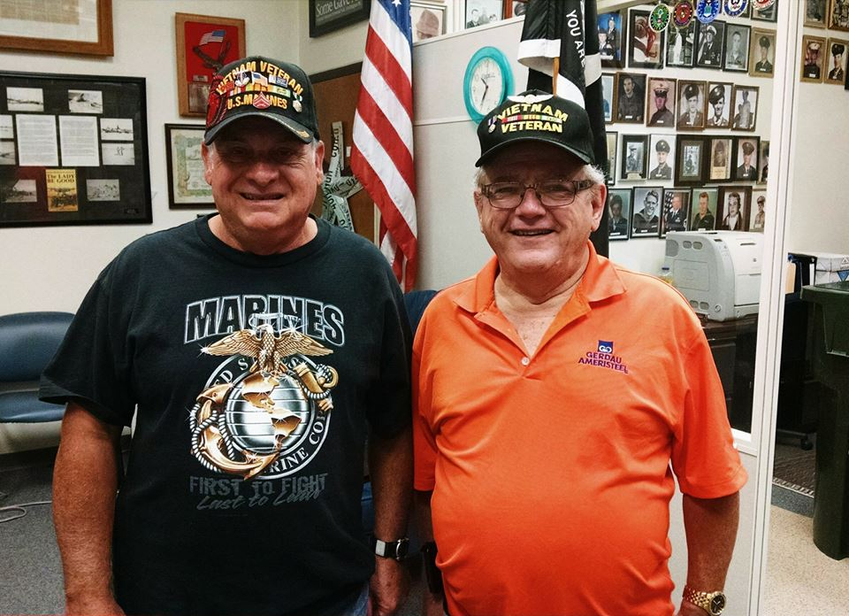 Two men wearing Vietnam Veteran hats smile into camera, standing in Veterans Affairs office