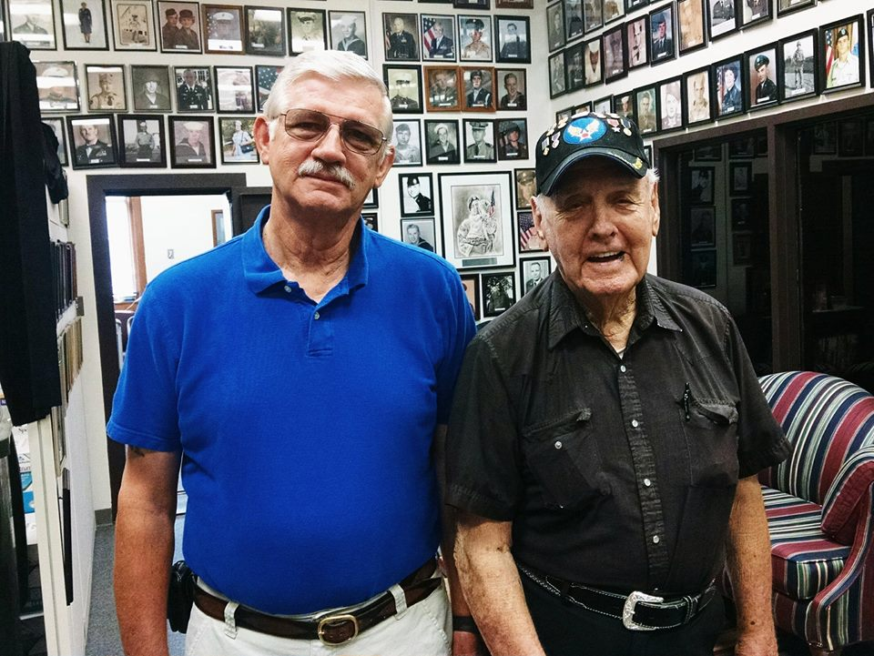 Man with glasses and blue shirt stands beside man in black shirt and veteran hat, both are looking into the camera smiling