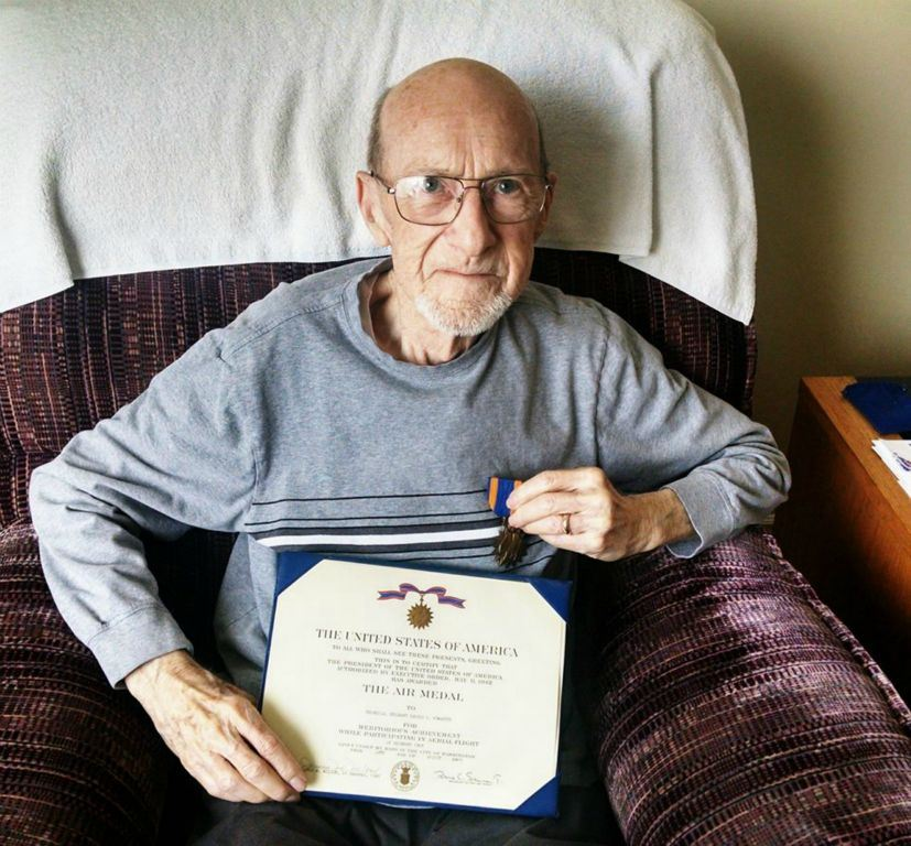 Up close of veteran with glasses, sitting in chair, holding certificate of the Air Medal and also holding the medal to his chest