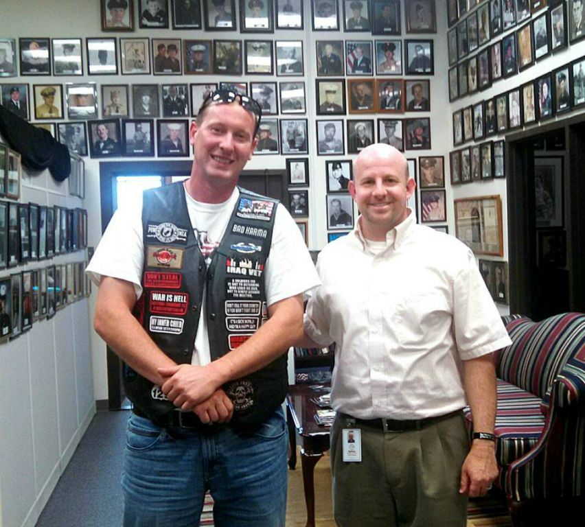Nathan Weinbaum stands with man in white shirt with black leather vest with patches, both men looking into the camera smiling