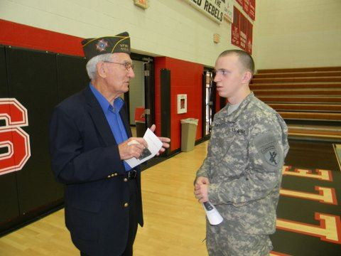 Older gentleman talks to young active duty soldier in uniform in a gym