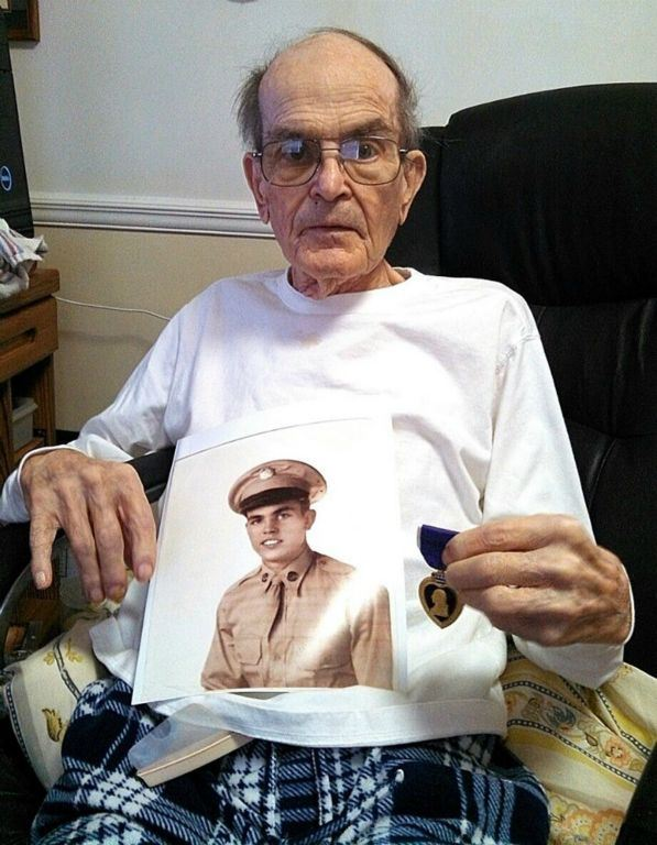 Up close image of veteran wearing white shirt and glasses, sitting in chair, holding sepia self-portrait and purple heart medal