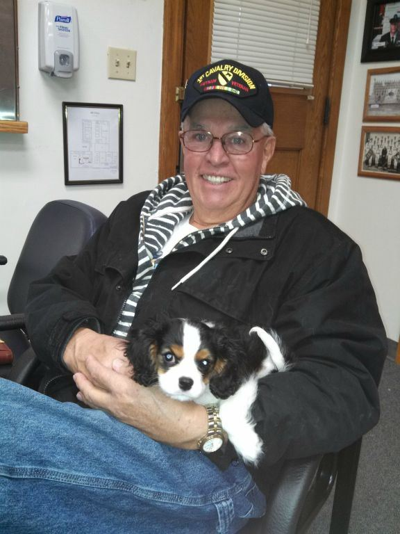 Smiling man in black jacket and glasses, with 1st Cavalry Division hat on, holds small spaniel in lap