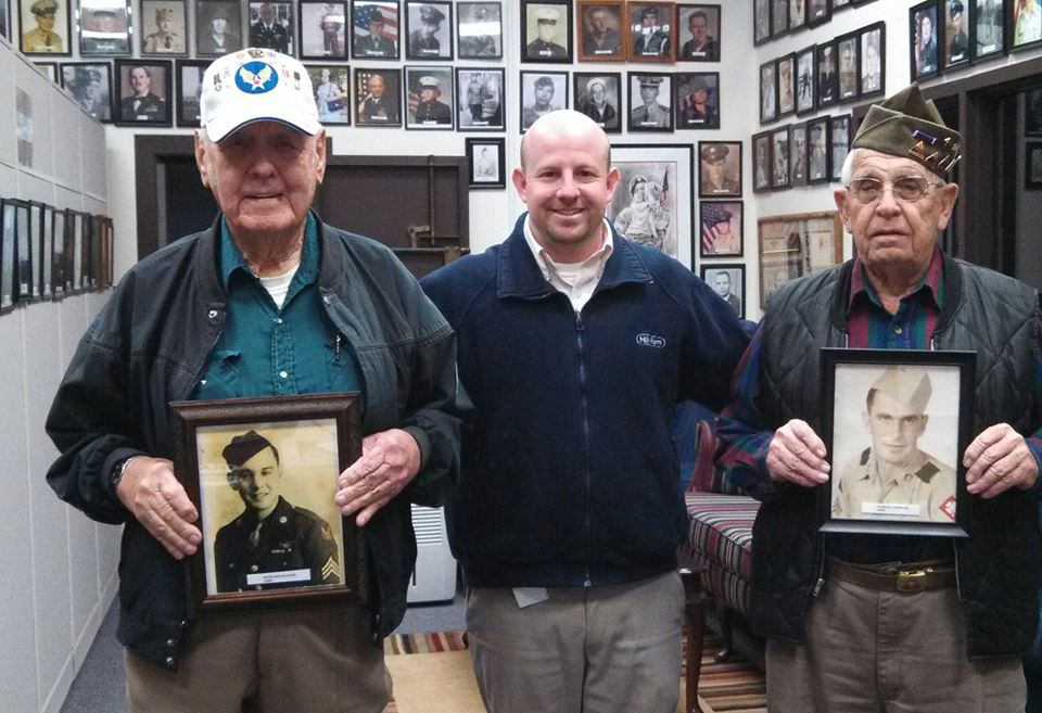 Nathan Weinbaum stnads between two veterans, both holding sepia self portraits in military uniform