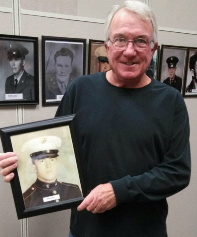 Man in black turtleneck stands in front of gallery of portraits, holding framed portrait of a marine