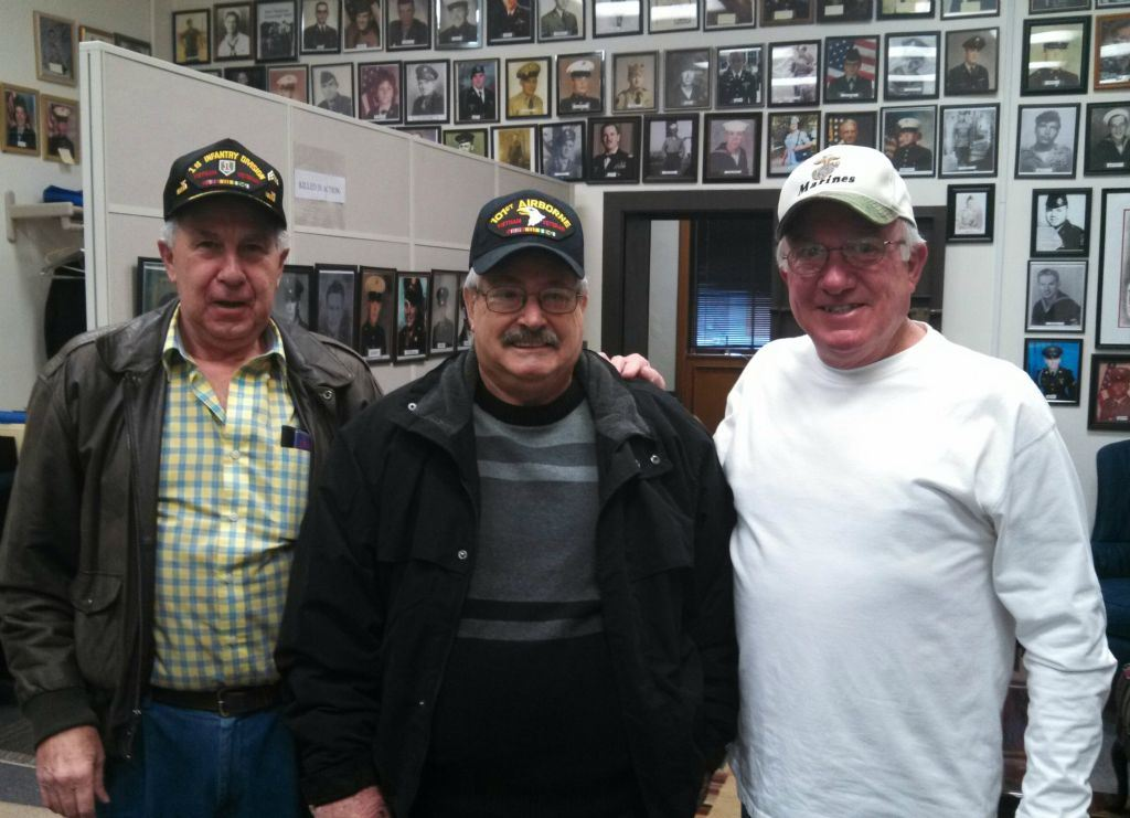 Three men stand together smiling, wearing hats 1st Infantry, 101st Airborne, and Marine