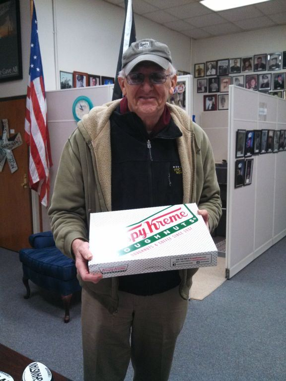 Man in Veterans Affairs office smiling, holding our Krispy Kreme doughnuts box