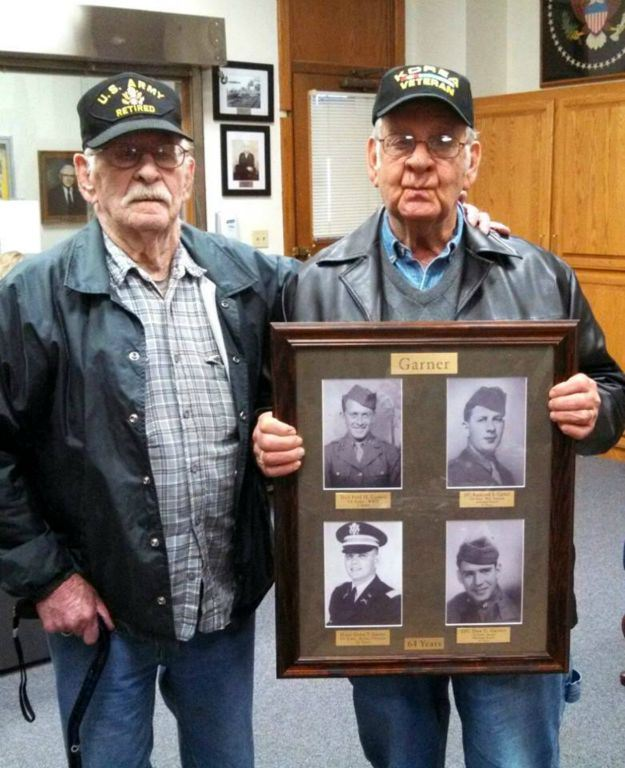 Two men stand together facing camera, one with a US Army Retired hat, and one with a Korea Veteran hat- who is also holding a frame with images of four soldiers with the name Garner