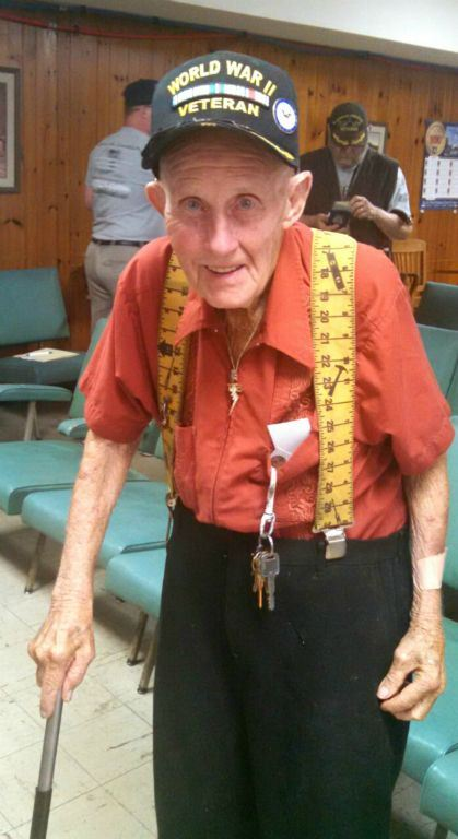 Man wearing orange shirt, yellow suspenders, and World War II Veteran hat, standing an dsmiling into camera