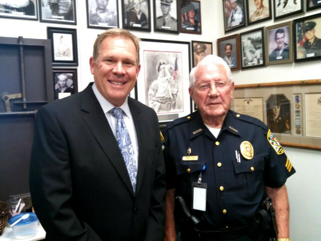 Man in suit smiles at camera standing beside Sheriff in uniform