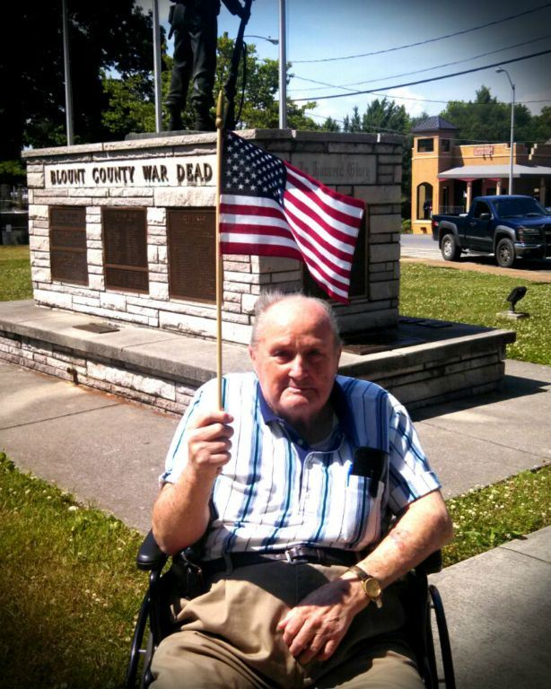 Man in stripe shirt, in wheelchair, holds up American flag in front of Blount COunty War Dead memorial