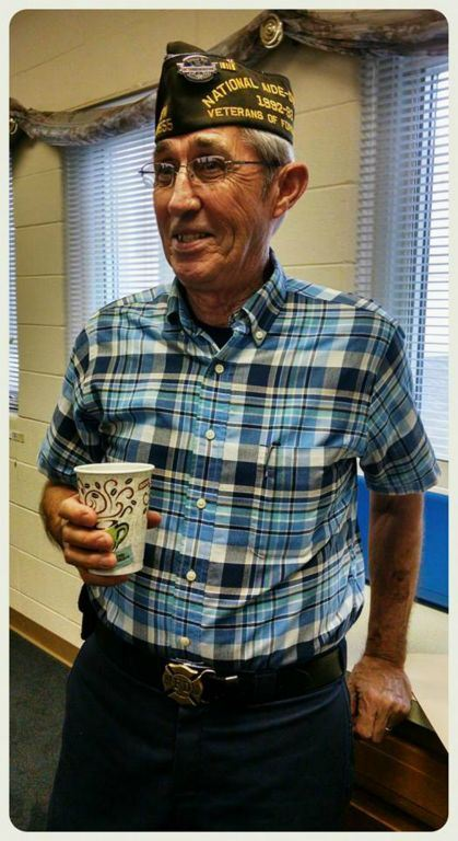 Man with glasses and VFW veteran hat smiles and holds a cup