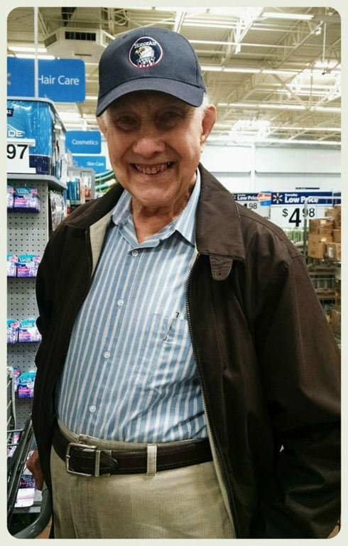 Veteran smiles into camera, standing in store, wearing blue shirt, brown jacket, and black hat