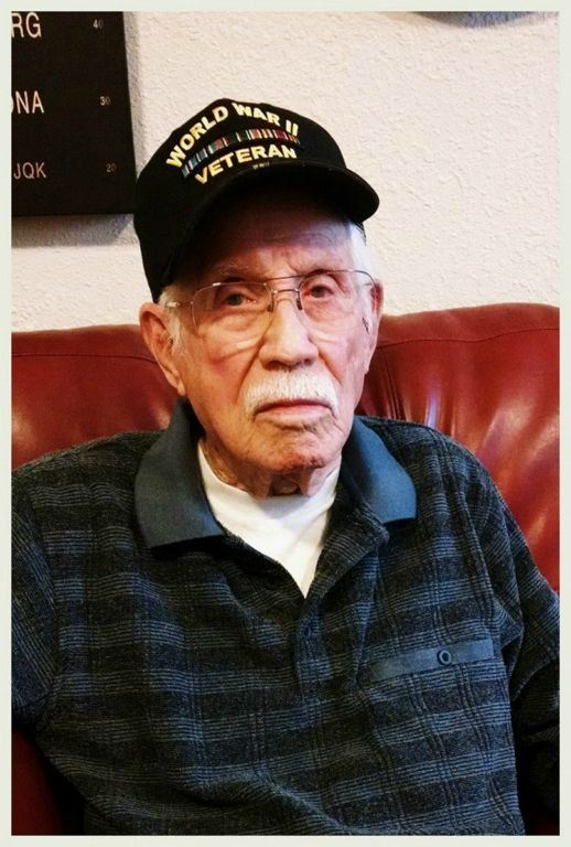 Up close portrait on man in glasses, wearing dark grey shirt and World War II veteran hat, sitting on red couch