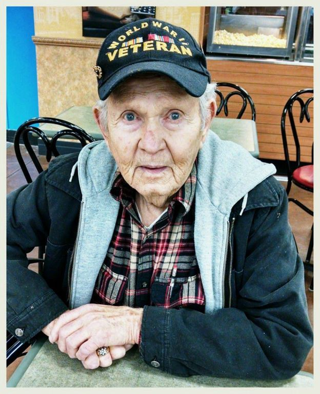 Up close portrait of a man sitting at a table, hands folded, looking into camera, wearing a World Ward II veteran hat