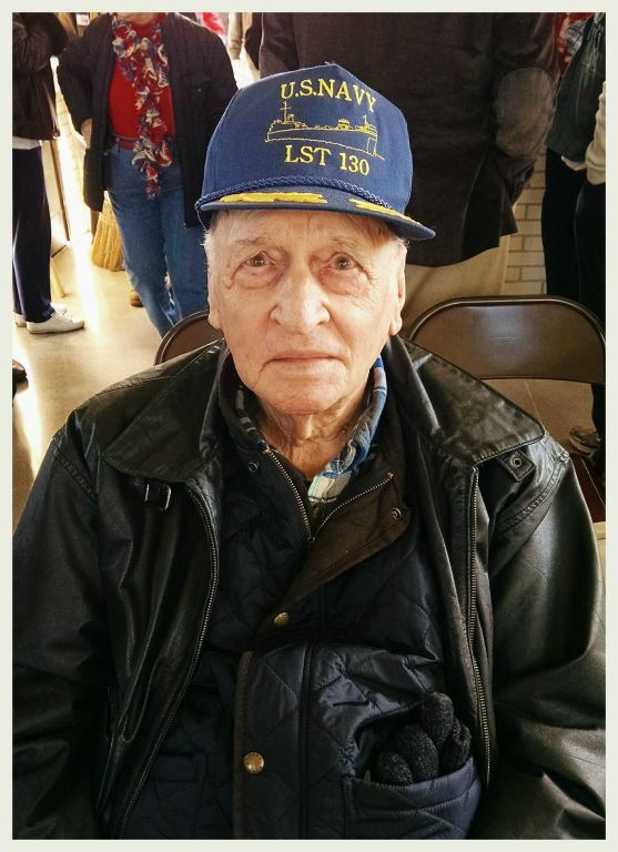 Up close picture of man wearing black leather jacket, and blue US Navy LST 130 hat, veteran is looking into camera