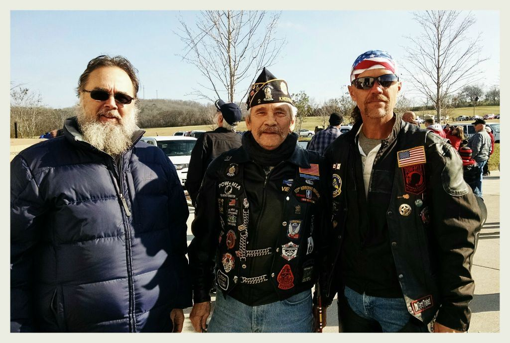 Three men standing beside each other in parking lot, looking into camera, two are weaing biker garb