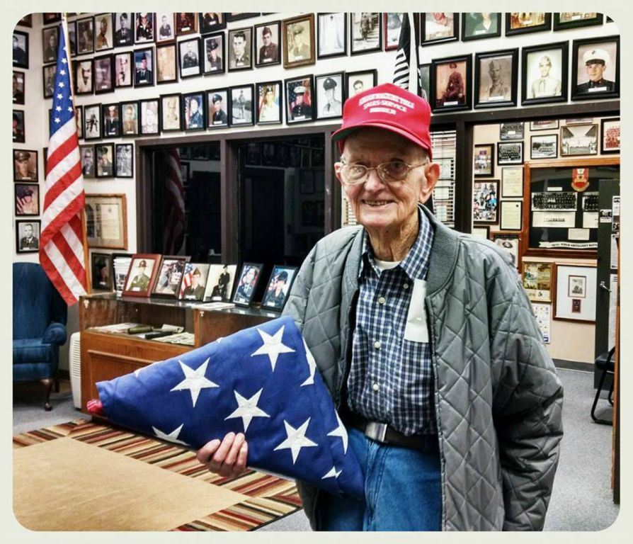 Veteran in glasses and plaid with red hat on holds folded American flag, looking into and smiling at camera