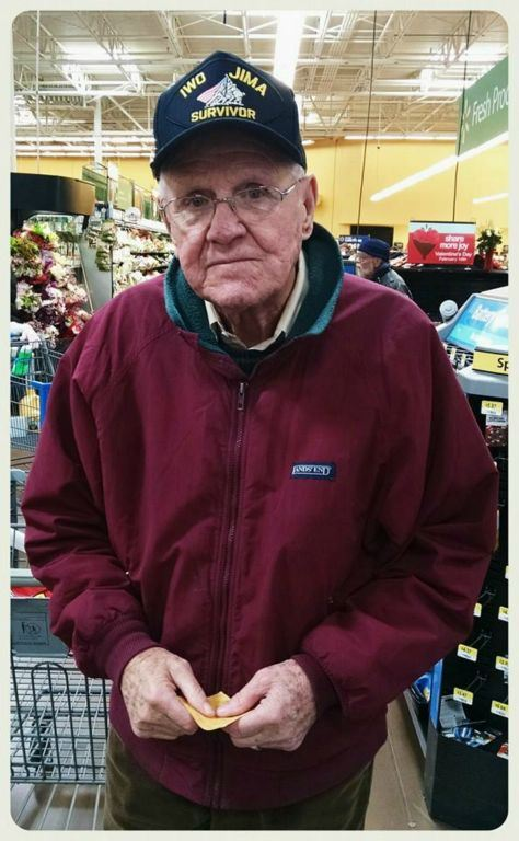 Man in maroon zippered jacket at store, looking into camera, wearing Iwo JIma Survivor hat