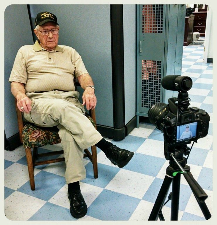 World War II Veteran sitting in chair wiating to have his picture taken