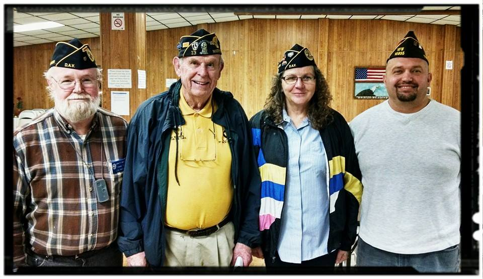 Three men and one woman veteran stand together smiling for camera
