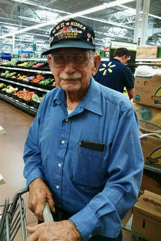 Man in blue shirt with glasses at grocery store wears hat with WWII, Korea, Vietnam Veteran, looking into camera smiling