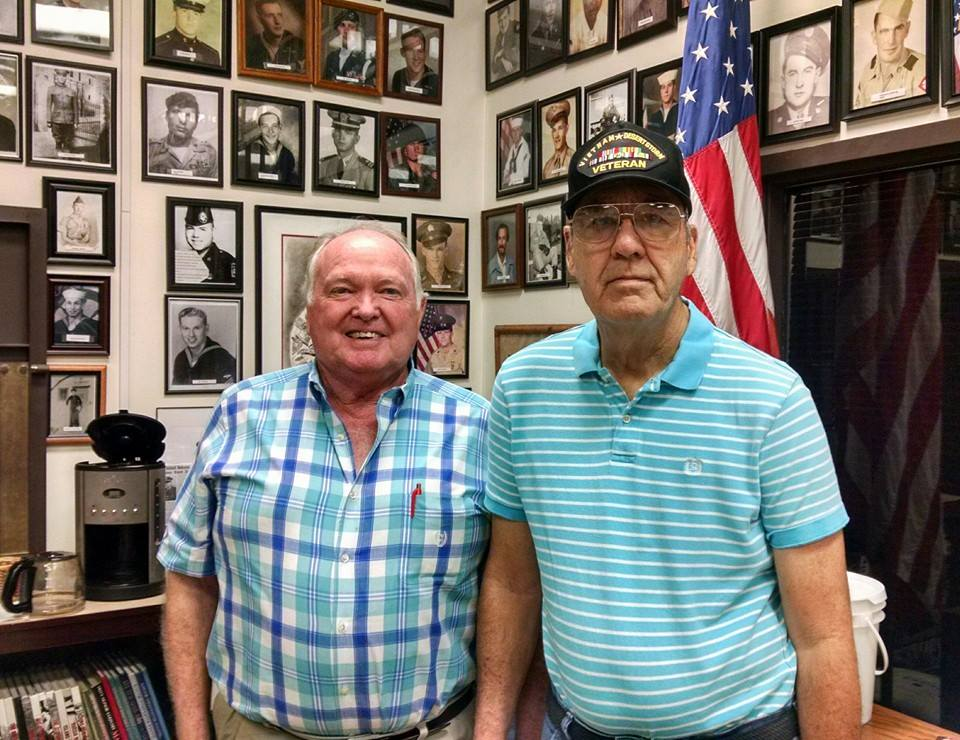At the Veterans Affairs office man in plaid stands smiling beside man in turquoise striped shirt and Vietnam Desert Storm hat