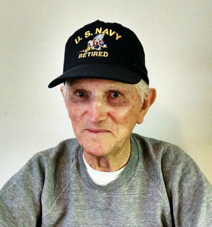 Up close portrait of man in grey sweater, wearing black US Navy retired hat, he is looking into camera smiling