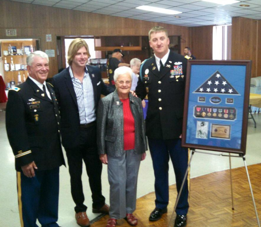 Two men in uniform flank a man in a suit and a woman in greay dress pants, beside them is a frame with American flag and medals and photograph of veteran