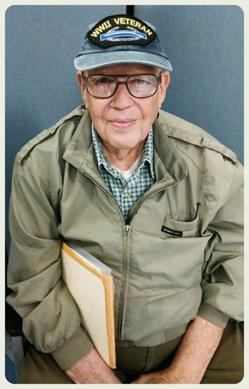 Portrait of veteran, wearing all khaki, glasses, and WWII Veteran hat, looking into camera